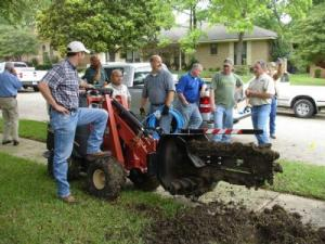 the Haltom City Irrigatin team take a break from trenching a new sprinkler line